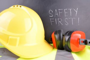 Safety first handwritten in white chalk with a yellow hard hat and red ear muffs in the fore ground.