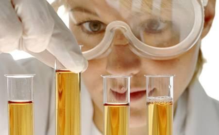 studentessa in laboratorio in primo piano con mascher protettiva occhi e provette