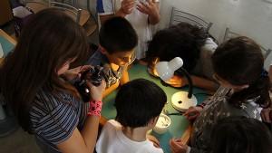 bambini che fanno esperimenti di scienze attorno ad un tavolo.
