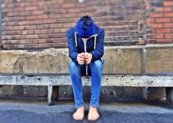 ragazzo triste su una panchina