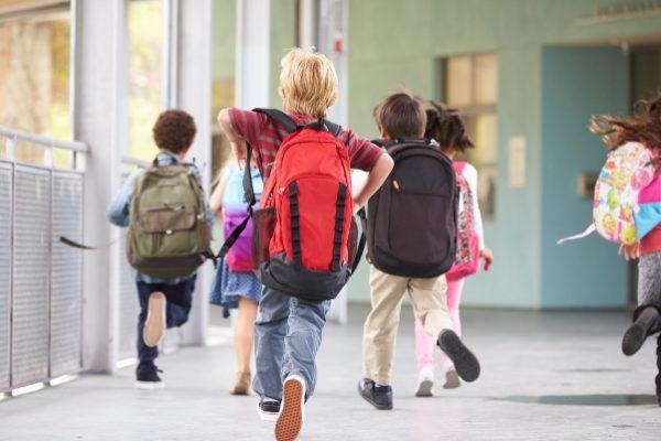 bambini che camminano con lo zaino in spalla